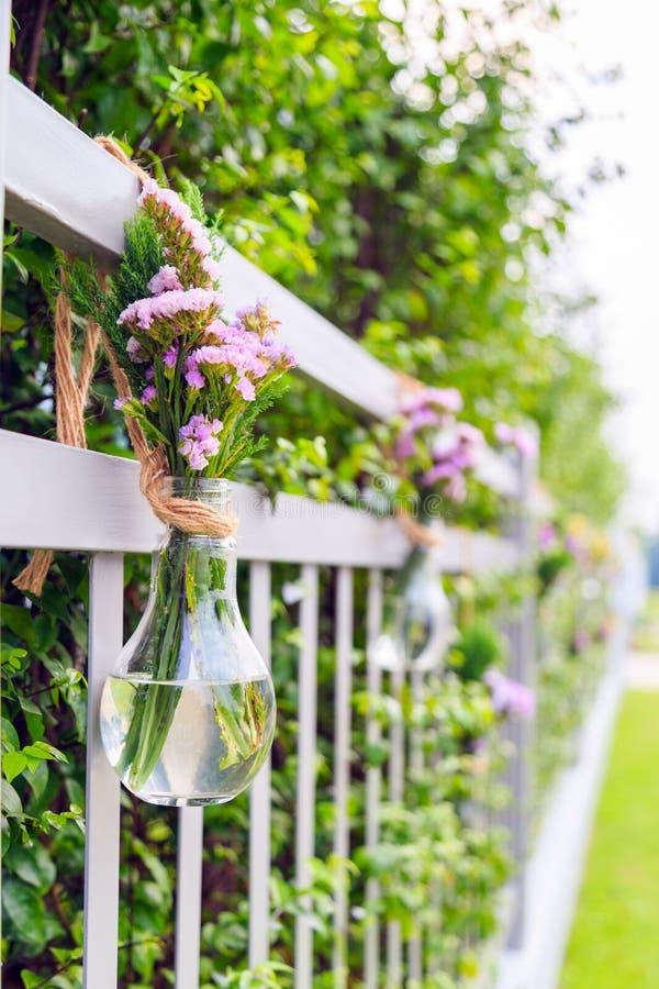 Un pourpre fleurit dans le vase formé à ampoule accrochant sur la barrière à la maison photo stock