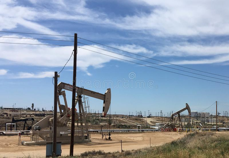 Un pozo de petróleo bombea el petróleo bruto de los campos, California fotografía de archivo