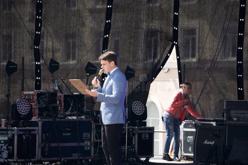 Un présentateur avec la main vers le haut de présenter l'exposé tandis que les personnes d'assistance observent dans la conférenc photo libre de droits