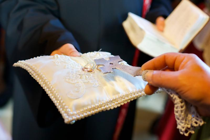 Un prêtre chrétien tient dans des ses mains un anneau de mariage image stock