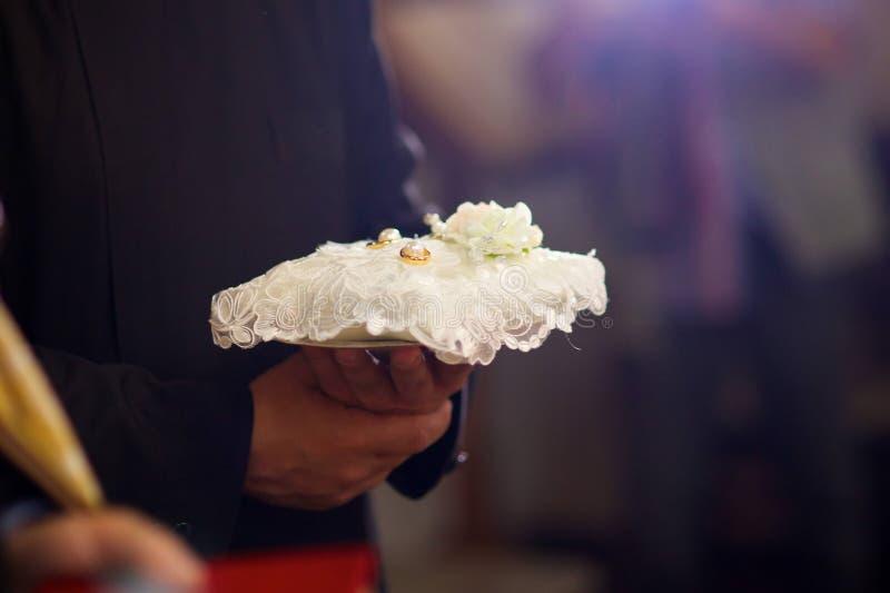 Un prêtre chrétien tient dans des ses mains un anneau de mariage photo stock
