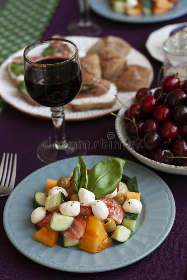 Un pranzo di buongusto per due persone: un'insalata, ciliegie fresche e vari aperitivi fotografie stock