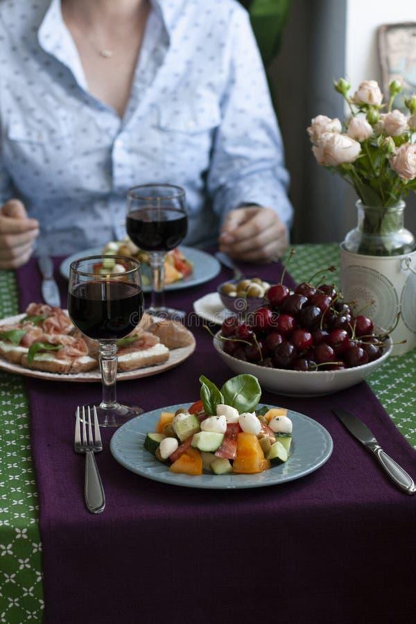 Un pranzo gastronomico per due: un'insalata, le ciliege fresche ed i vari aperitivi fotografie stock