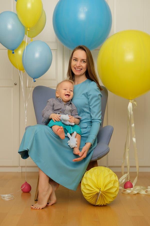 Un premier anniversaire de bébé garçon an Enfant d'enfant en bas âge avec la mère s'asseyant dans la chaise photo stock