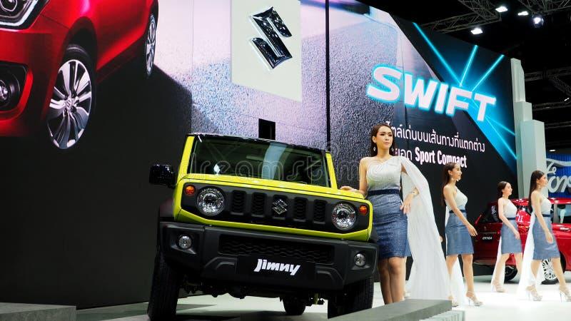 Un presentador femenino se coloca al lado de Suzuki Jimny imagen de archivo libre de regalías