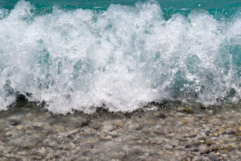 Un primer de guijarros y de la espuma del mar Ondas que salpican y que salpican contra la orilla, lanzamiento macro imagen de archivo