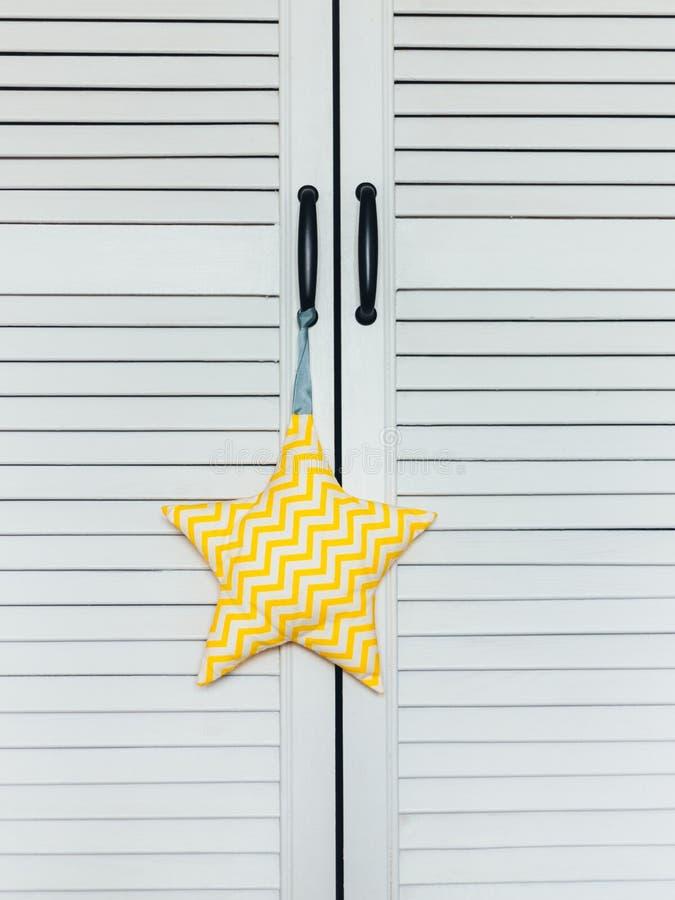 Un primer de un juguete suave blanco-amarillo de la estrella cuelga en la manija de una gabinete-pantalla blanca fotografía de archivo libre de regalías