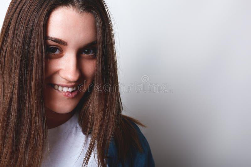 Un primer de la muchacha bonita con el pelo marrón y los ojos atractivos grandes que tienen sonrisa encantadora que muerde su lab fotos de archivo libres de regalías