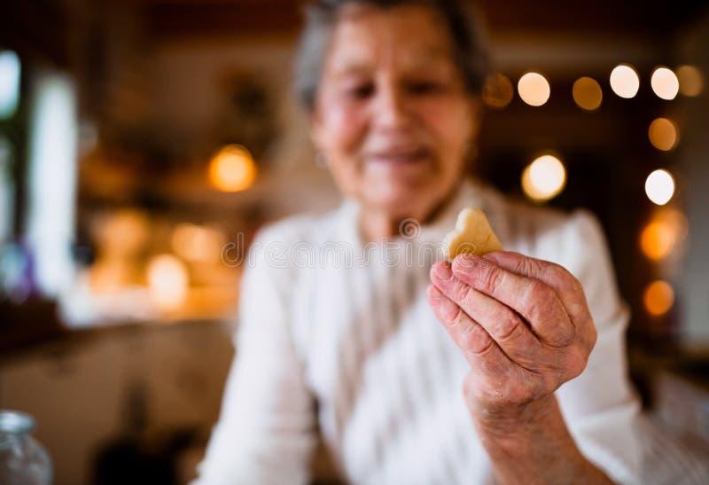 Un primer de la mujer mayor que hace las tortas en una cocina en casa, sosteniendo una galleta fotografía de archivo
