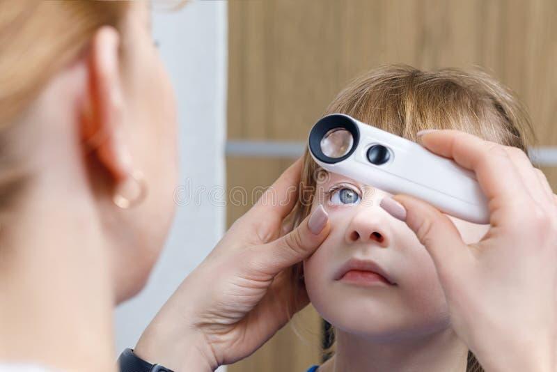 Un primer de un oftalmólogo que comprueba el ojo de un niño fotos de archivo