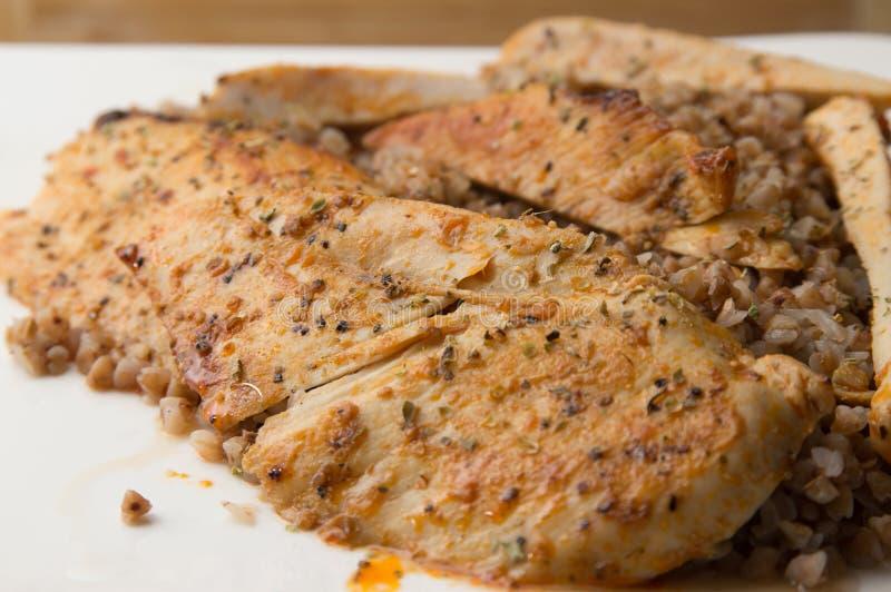 Un primer de un risotto del alforfón con las pechugas de pollo asadas a la parrilla y fritas en una placa foto de archivo libre de regalías