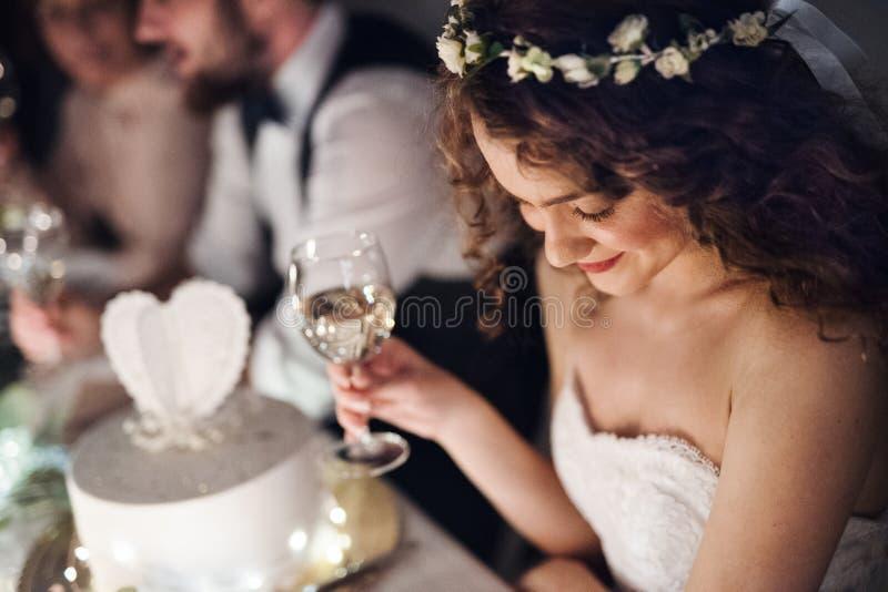 Un primer de una novia joven que se sienta en una tabla en una boda, sosteniendo una copa de vino imagenes de archivo