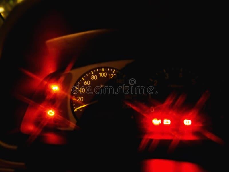 Un primer de un velocímetro de un innight del coche, con el centelleo de las lámparas rojas fotografía de archivo