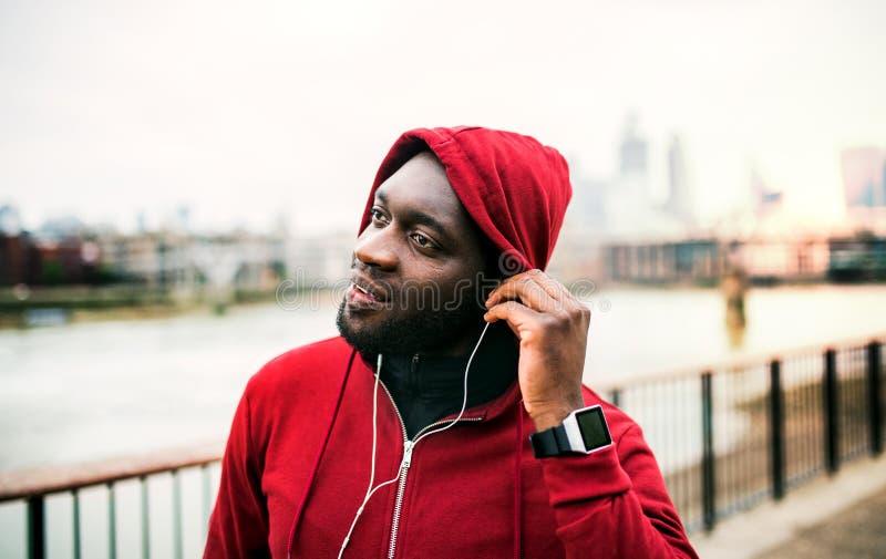 Un primer del corredor del hombre negro con los auriculares y la capilla en su cabeza en una ciudad Copie el espacio imagenes de archivo