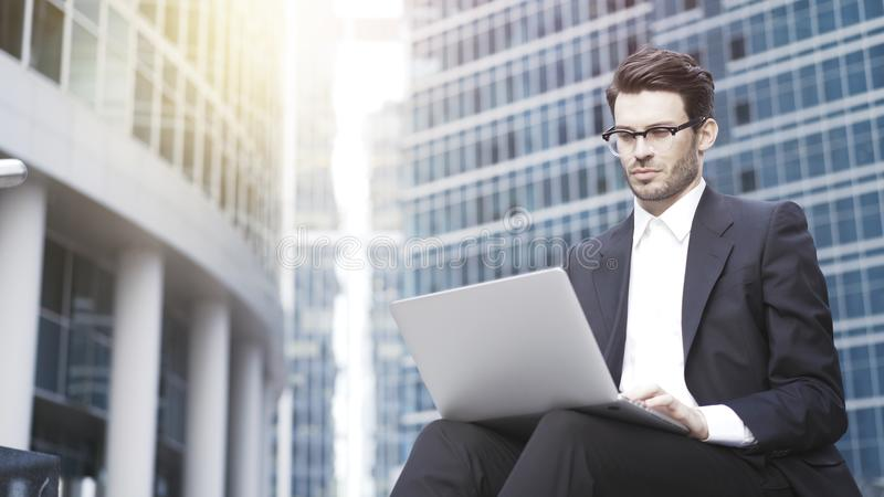 Un primer del hombre de negocios hermoso joven con el ordenador portátil afuera foto de archivo