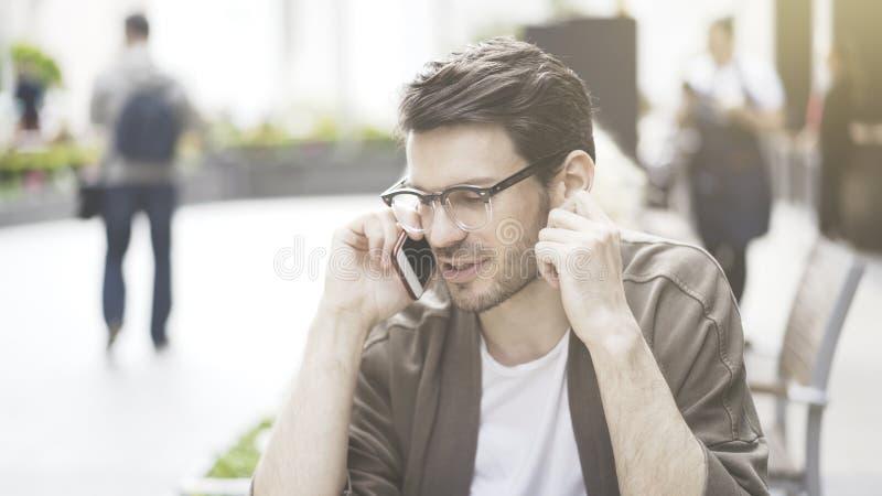 Un primer del hombre joven serio que habla en el teléfono que tiene una llamada fotos de archivo