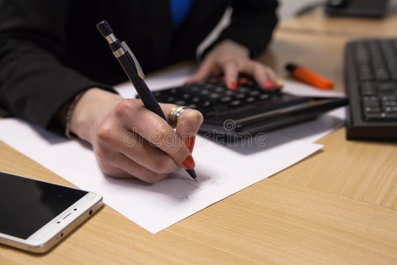 Un primer, señora del negocio, escribiendo en un trozo de papel, se sienta en su escritorio foto de archivo