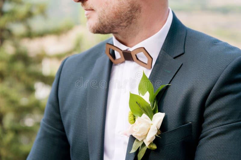 Un primo piano del mento di uno sposo alla moda barbuto per correggere una farfalla con un occhiello nel telaio fotografia stock