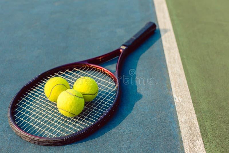 Un primo piano dell'angolo alto di tre palline da tennis su una racchetta professionale immagine stock libera da diritti