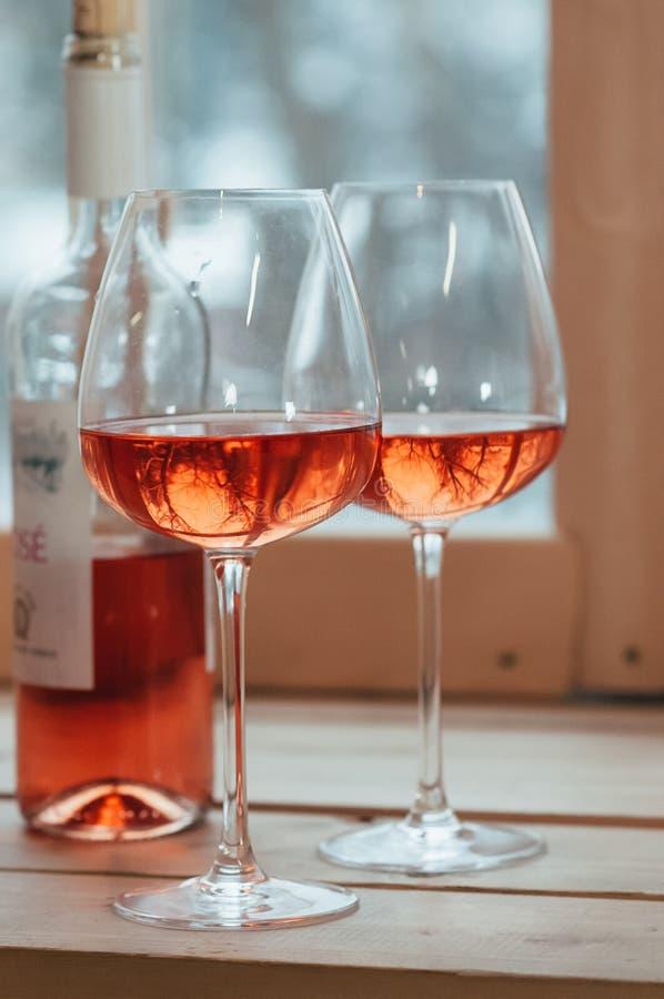 Un primo piano della bottiglia e di due di vino rosato ha riempito i vetri immagine stock libera da diritti