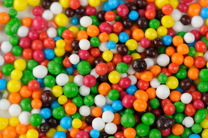 Lo zucchero multicolore spruzza (il primo piano delle decorazioni commestibili del bigné) fotografia stock