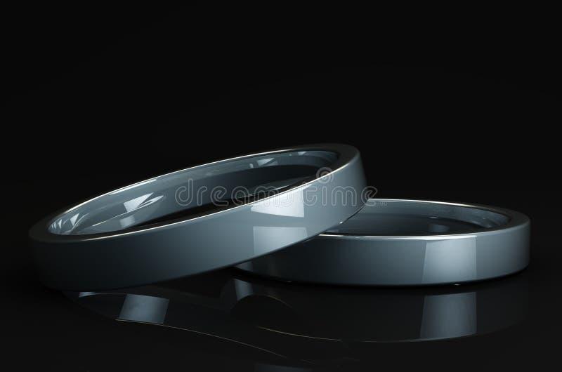 Un primo piano di 2 anelli d'argento riflettenti sul nero Shinny la superficie fotografie stock