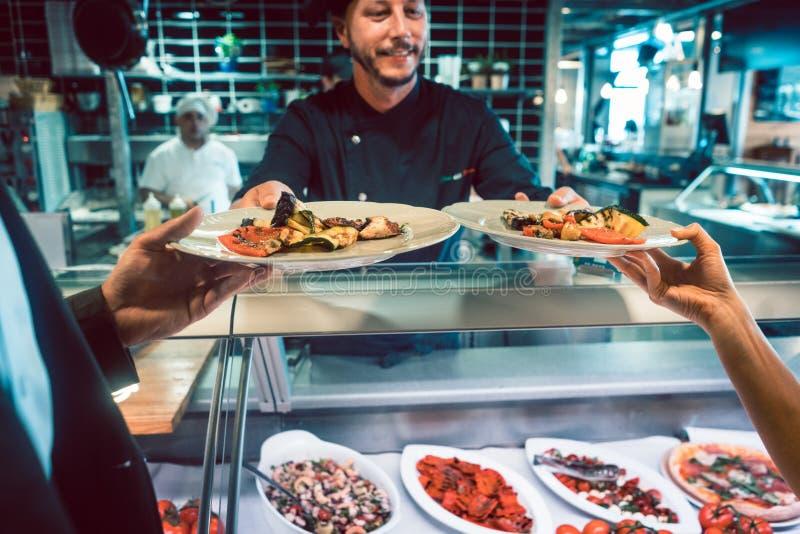 Un primo piano di due piatti con frutti di mare e le verdure è servito da un cuoco unico con esperienza immagine stock libera da diritti
