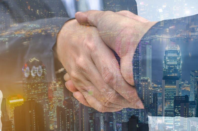 Un primo piano di due uomini d'affari che stringono le mani contro il backgroun bianco fotografia stock
