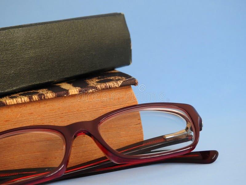 Un primo piano di due vecchi libri ed occhiali su un fondo blu fotografia stock