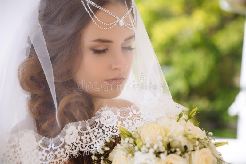 Un primo piano di giovane sposa la ha chiuso occhi dalle sensibilità che la sopraffanno, sta preparando entrare nella chiesa, ha  immagine stock