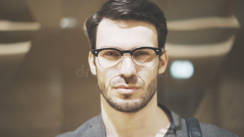 Un primo piano di giovane uomo barbuto che esamina la macchina fotografica fotografia stock