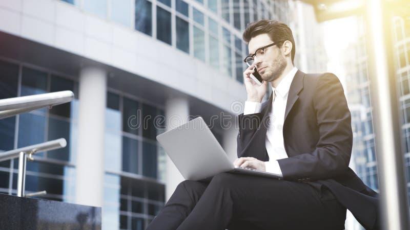 Un primo piano di giovane uomo d'affari bello con il computer portatile che ha una chiamata fotografia stock