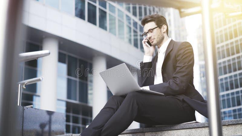 Un primo piano di giovane uomo d'affari con il computer portatile che ha una chiamata immagini stock