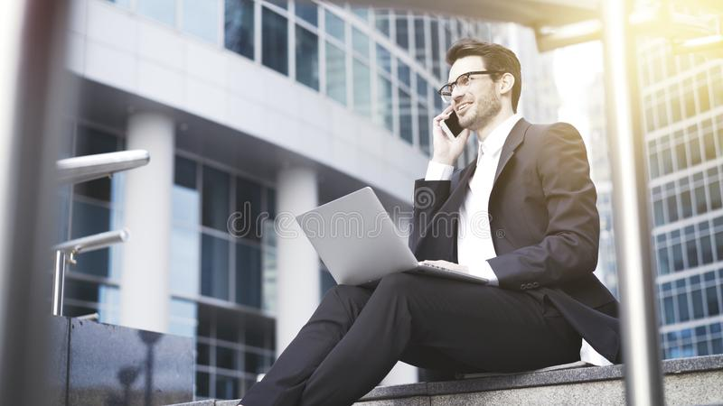 Un primo piano di giovane uomo d'affari felice con il computer portatile che ha una chiamata immagine stock libera da diritti