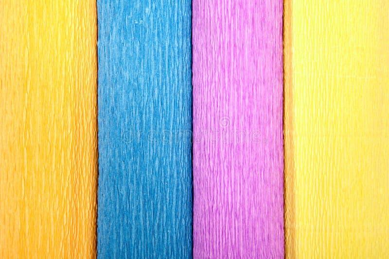 Un primo piano di quattro ha colorato i rotoli della carta crespa, struttura per il contesto immagini stock
