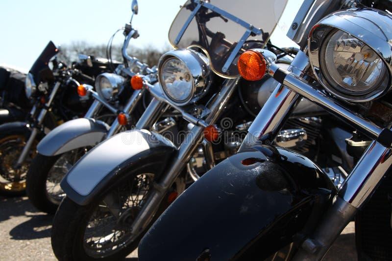 Un primo piano di quattro motocicli, stante in una fila immagini stock libere da diritti