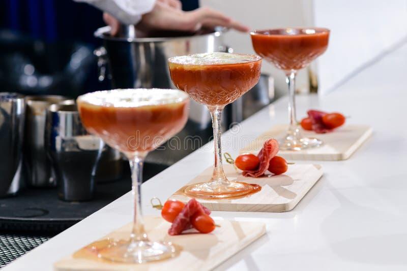Un primo piano di tre vetri di martini con il cocktail rosso sul conteggio della barra immagini stock