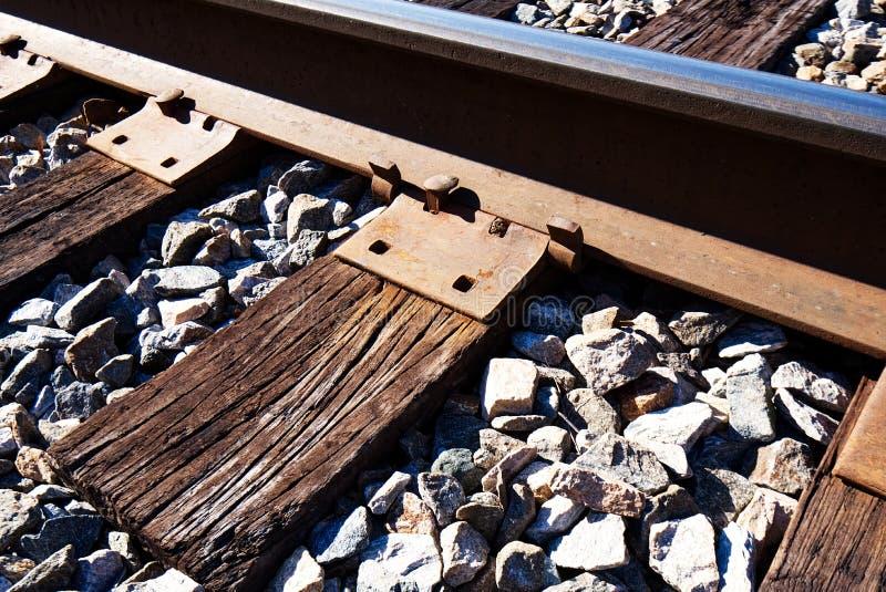 Un primo piano di una ferrovia della ferrovia, dei legami trasversali stagionati e di una zavorra immagini stock libere da diritti