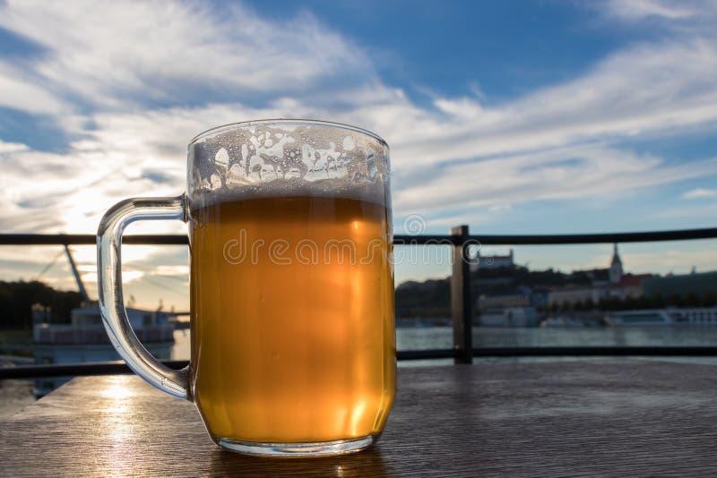 Un primo piano di una tazza di birra fredda con schiuma e gocce di acqua sul cielo blu del fondo e le nuvole bianche ed il sole immagine stock libera da diritti
