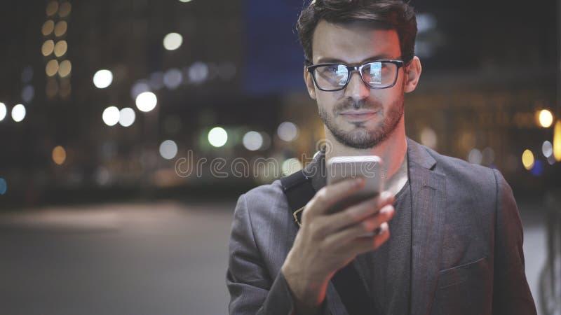 Un primo piano di un uomo con un cellulare alla notte sulla via immagini stock