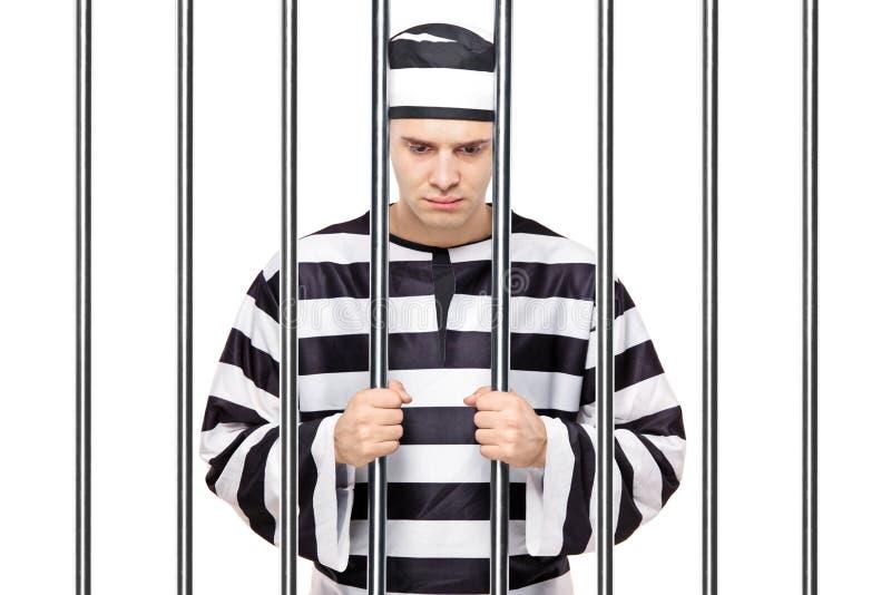 Un prisonnier triste dans des bars de fixation de prison photos stock
