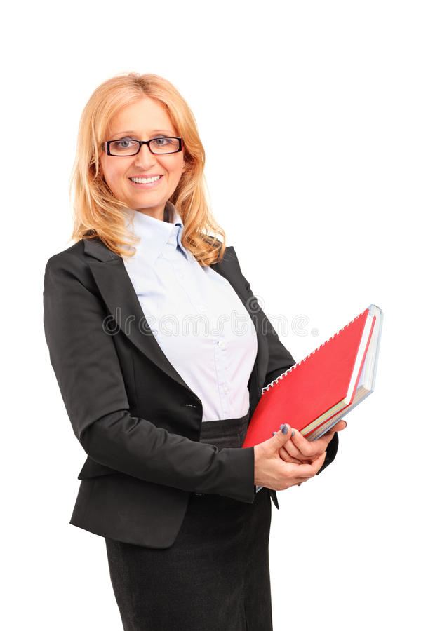 Un profesor de sexo femenino sonriente que sostiene un cuaderno fotos de archivo