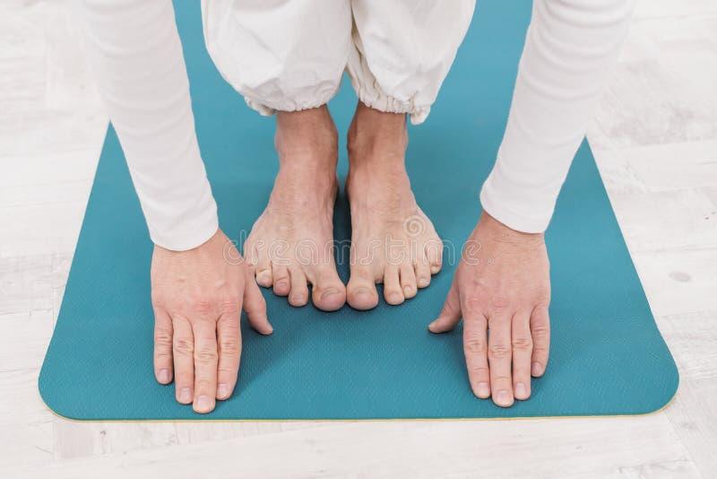 Un profesor de sexo masculino y un instructor en la ropa blanca están presentando un amarillo y una estera azul de la yoga, prepa foto de archivo libre de regalías