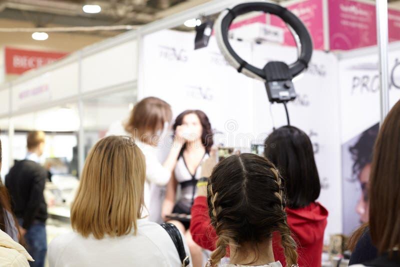 Un profesor profesional del maquillaje enseña a un grupo de estudiantes al bec fotos de archivo