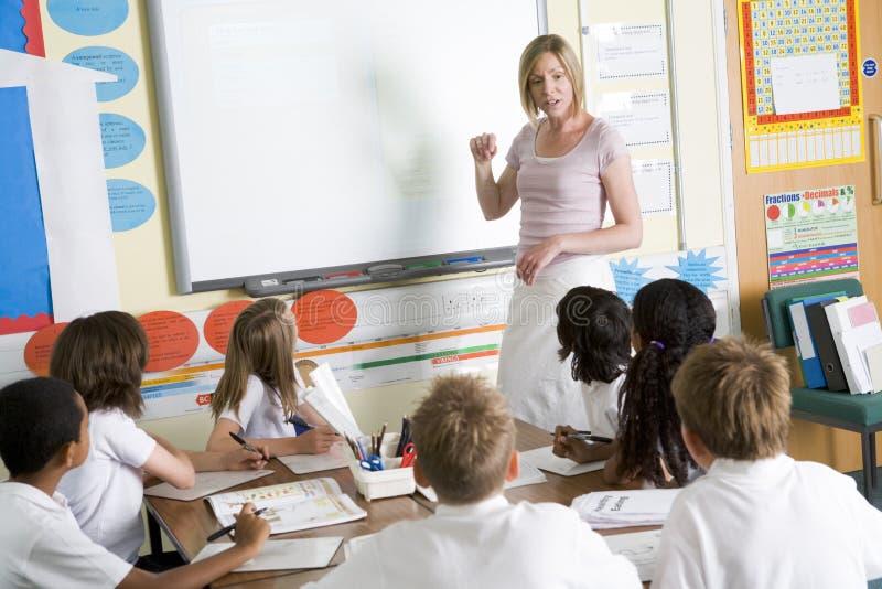 Un professeur enseignant une classe d'école junior photos stock