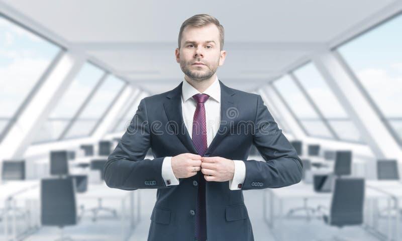 Un professionnel beau se boutonne vers le haut du costume Bureau panoramique moderne lumineux de grenier de toit photo stock