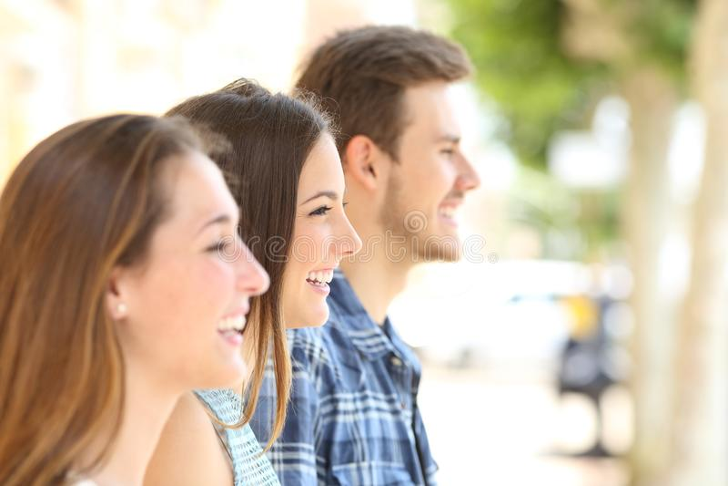 Un profilo di tre amici che distolgono lo sguardo nella via immagine stock