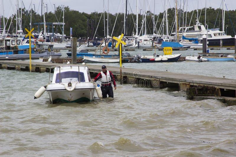 Un propriétaire de bateau apportant son petit bateau de fibre de verre vers le rivage à Warsash, Hampshire à une remorque de atte photographie stock