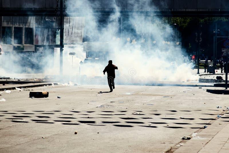 Un protestataire essayant de s'?chapper de la larme ? gaz par la police pendant les protestations de parc de Gezi ? Ankara, rue d photo stock