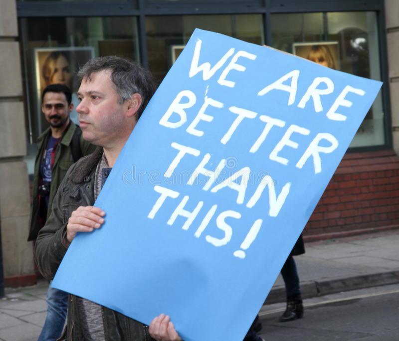 Un protestataire tient un signe optimiste à un rassemblement d'Anti-atout photos libres de droits